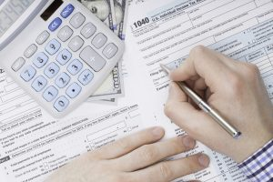 Close up shot of a male filling out US 1040 Tax Form next to calculator and 100 dollars banknote under it
